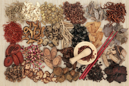 Traditional chinese herbal medicine ingredients over bamboo background with mortar and pestle and chopsticks.