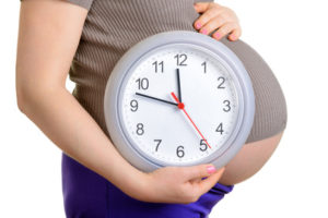 Pregnant woman holding wall clock. It's time. Isolated on white.