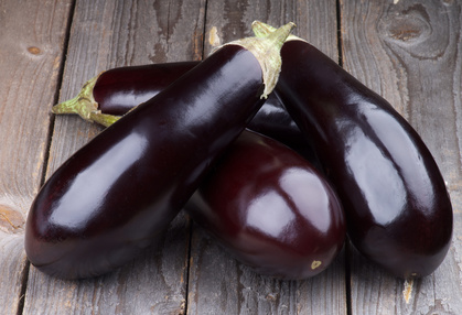 Heap of Fresh Ripe Eggplants isolated on Rustic Wooden background